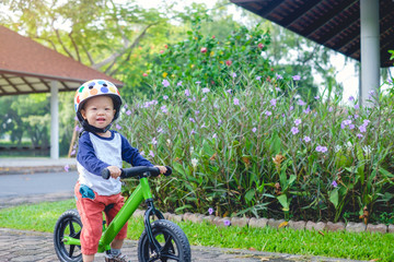 Cute little Asian 1 years / 18 months old baby boy child wearing safety helmet learning to ride his first balance bike in spring time, kid playing & cycling in garden, Child first experience concept