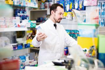 Smiling man pharmacist looking rows of drugs