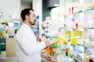 Male pharmacist checking assortment of drugs