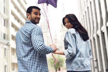 Romantic couple holding hands walking around the city.