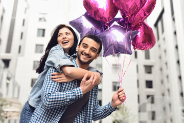 Romantic couple walking along alley with balloons.