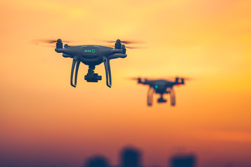Close up photo of two Professional Remote Control Air Drones with action cameras flying in dramatic sunset sky. Modern technologies. Travel, hobby, inspiration. Pastel orange toning. Kiev, Ukraine Wall mural