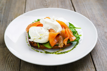 Healthy breakfast, restaurant menu photo, delicious meals with proteins and low fat. Wholemeal bread toast and poached egg with smoked salmon and green salad,