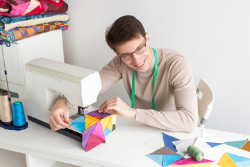 quilting, hobby, passion concept. there is a professional tailor, a young man with adorable smile, who is sitting at his table and stitching patches for feature blanket