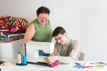 family business, patchwork, occupation concept. there is coworking couple, a young man who is learning to stitching on the sewing machine and an old lady, his grandma, she is an experiences seamstress