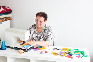 profession, business, patchwork concept. there is a strict woman in eyeglasses with green string, she is working with sewing machine at sitting at the white work table equiped all the tools she need