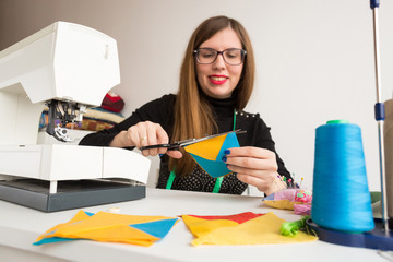 technique, sewing, arrangement concept. sitting at a table young woman with long hair and bright red lips is working crafting quilt made of different patches in yellow and blue coloures