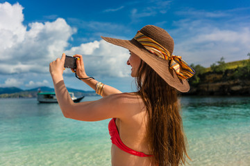 Cheerful young woman taking pictures with a compact camera in a sunny day during summer vacation in Komodo Island, Indonesia