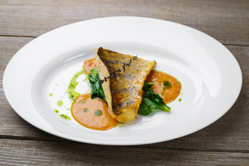 Delicious fish with spinach garnishing and sauce. Mediterranean cuisine, main dish, banquet, food photo, fish restaurant menu concept