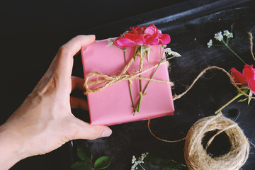 Pink gift box wrapped with twine bow and rose flowers
