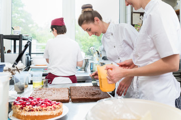 Three pastry bakers in confectionary preparing fruit pies for later sale