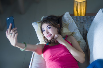 young beautiful and happy hispanic woman lying at home sofa couch taking selfie portrait picture or having internet video call with mobile phone