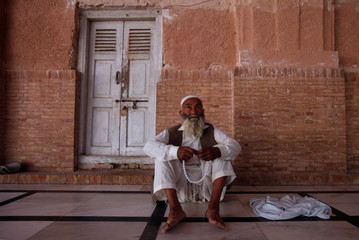 An elderly man holds his tesbih as he sits at the premises of the Mahabat Khan Mosque in Peshawar
