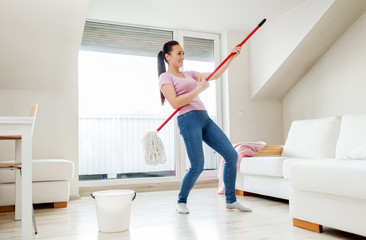 people, housework and housekeeping concept - happy woman or housewife with mop cleaning floor and having fun at home
