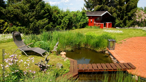 naturbelassener Gartenteich mit Brücke und Margeritenwiese sowie ...