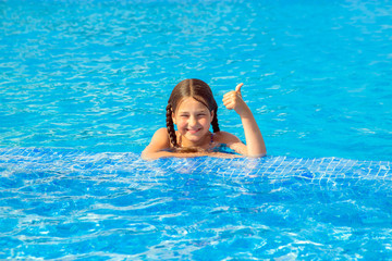 Kid swims in the pool and shows thumb up symbol.