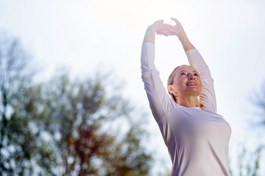 Morning gymnastics. Nice cheerful woman holding her hands up while doing morning exercises