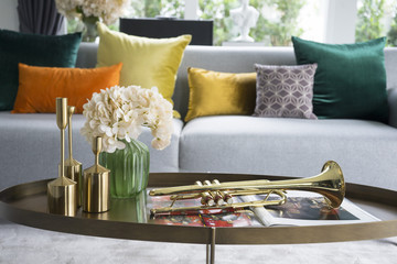 colorful and stylish living room with flower vase and gold trumpet on table.
