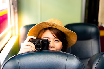 Beautiful traveler woman is hiding behind chair and taking photo someone. Charming beautiful woman feels happy and joyful. Pretty girl is sitting on train for traveling to tourism location. copy space