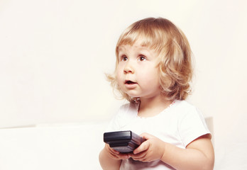 Portrait of a cute little girl in a white dress holds a tv remote on white background.