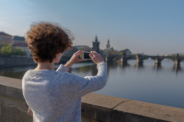 A female tourist makes a photo on a mobile phone in the background of Prague. Tourism in Europe, a woman is walking around the city with a mobile phone