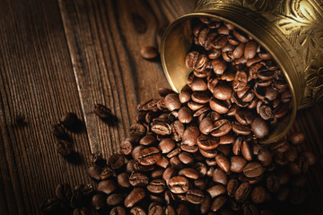 Roasted Coffee Beans (Arabica) In A Gold Metallic Cup On A Wooden Board. Background Series. Shallow Depth Of Field.
