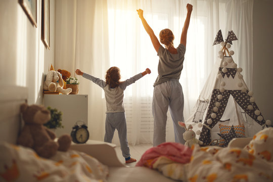 mother and   daughter stretch themselves after waking up in the morning