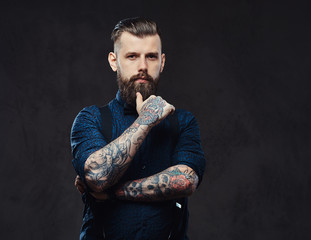 Pensive handsome old-fashioned hipster in a blue shirt and suspenders, standing with hand on chin in a studio.