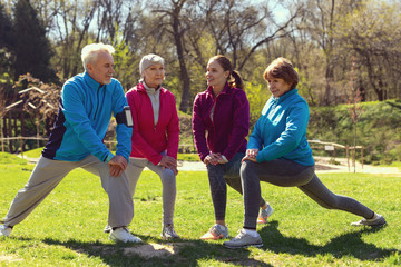 Good shape. Content athletic woman smiling and training aged people in the open air