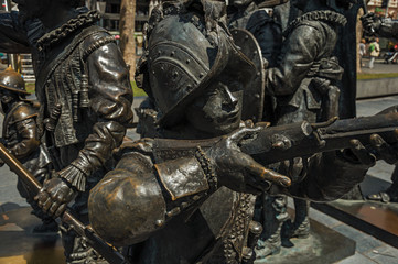 Bronze sculpture of XVII century soldiers on the Rembrandt Square in a sunny day at Amsterdam. The city is famous for its huge cultural activity, graceful canals and bridges. Northern Netherlands.