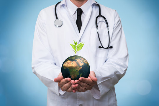 Doctor holding a planet earth globe in his hands. Environment and healthy concept for global ecology