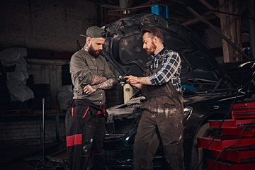 Two mechanic talking during repairs a broken car in a garage.