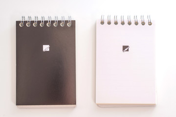 """""""Business concept - Top view collection of black spiral notebook on white  background desk for mockup"""""""