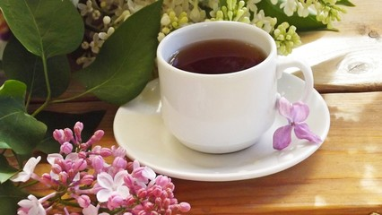 A Cup of tea on a wooden table and a bouquet of lilacs.