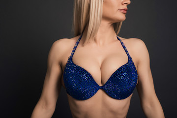 Close up Perfect body Fitness woman bodybuilder in blue swimsuit isolated posing over black background in studio.