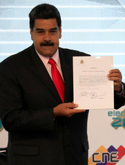 Venezuela's re-elected President Maduro holds a certificate confirming him as winner of Sunday's election, in Caracas