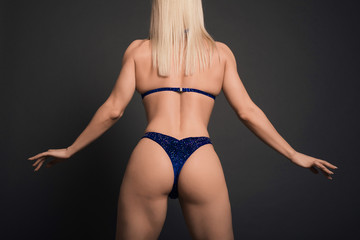 Close up Perfect body Fitness woman bodybuilder in blue swimsuit isolated posing back over black background in studio.