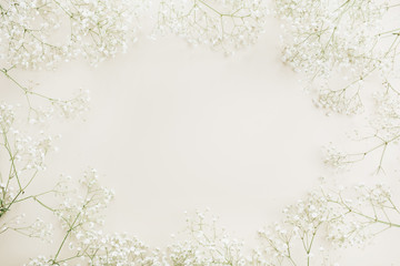 Frame with copy space of white gypsophila flower bouquet pattern. Flat lay, top view festive background.