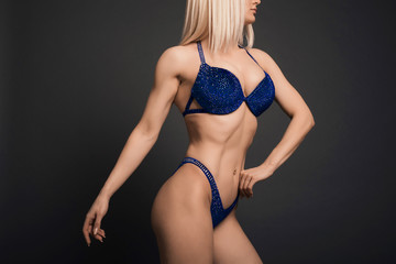 Perfect body Fitness woman bodybuilder in blue swimsuit isolated posing over black background in studio.