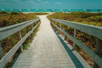 Dramatic View of Wood Bridge looking toward a Sandy Ocean Beach with Colorful Umbrellas on a Sunny Day
