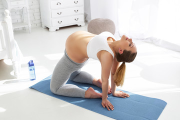 Measure of comfort. Top view of calm pregnant woman inhaling and trying yoga