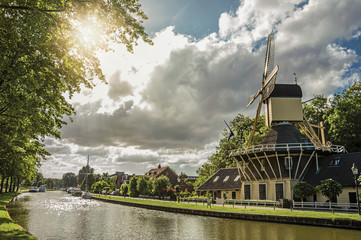 Wide tree-lined canal with windmill and boats and shine of sunset reflected in water at Weesp. Quiet and pleasant village full of canals and green near Amsterdam. Northern Netherlands. Retouched photo