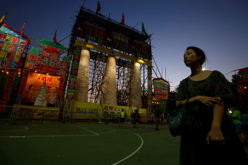 A woman stands in front of bun towers during Bun Festival at Cheung Chau island in Hong Kong