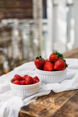 Beautiful juicy fresh strawberries in white bowl on wooden background, summer concept