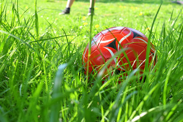 Close up view of red ball on green grass. Playing Exercise Football Concept