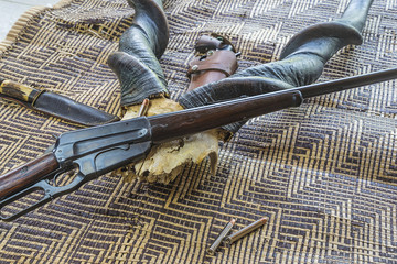 Lord Derby eland antlers and hunting carbine on african mat