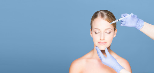 Doctor injecting in a beautiful face of a young woman. Plastic surgery concept.