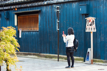 A woman with a camera on the background of a blue building and a tablet with pictonrames, Kyoto, Japan. Copy space for text.