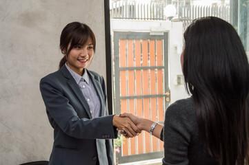 Businesswomen and partner shaking hands in office.