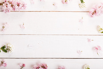 Festive wild spring summer flowers, lilac composition on the white wooden background. Overhead top view, flat lay. Copy space. Birthday, Mother's, Valentines, Women's, Wedding Day concept.